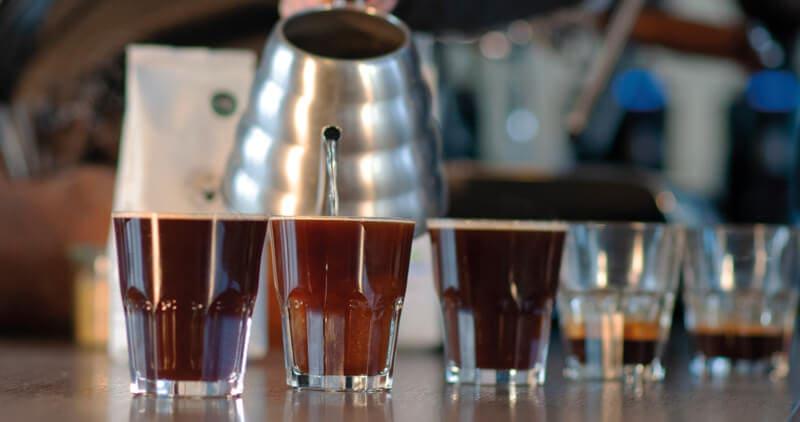 mehrere Gläser mit Kaffee befüllt, Metallkanne im Hintergrund, aus der Wasser in die Gläser gegossen wird