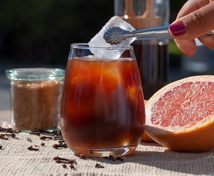 Glas mit Cold Brew Getränk, in das eine Hand von oben mit einer Zange einen Eiswürfel gibt