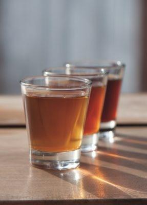 drei Glaeser hintereinander, gefuellt mit unterschiedlich hellem Cold Brew