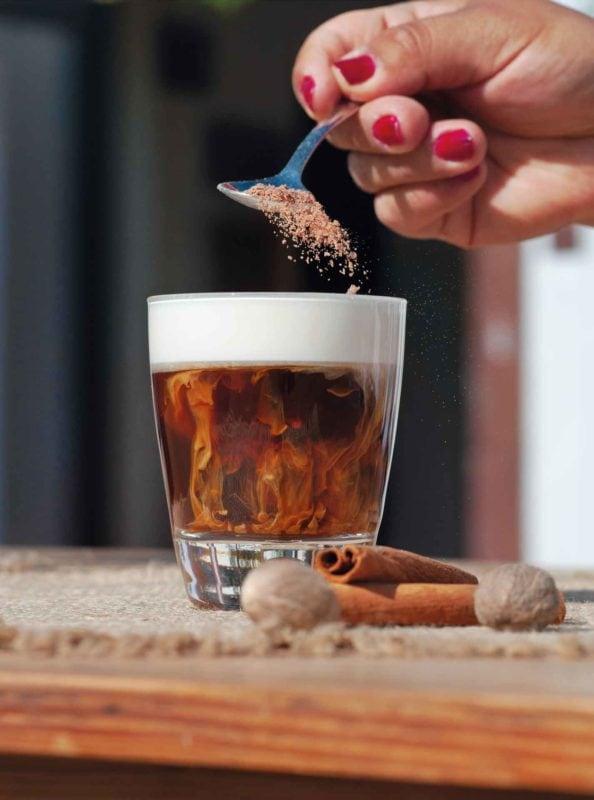 Glas gefüllt mit klarem Kaffee und Milchschaumhaueb, darüber eine Hand mit Löffel, aus dem brauner Zucker runterrieselt