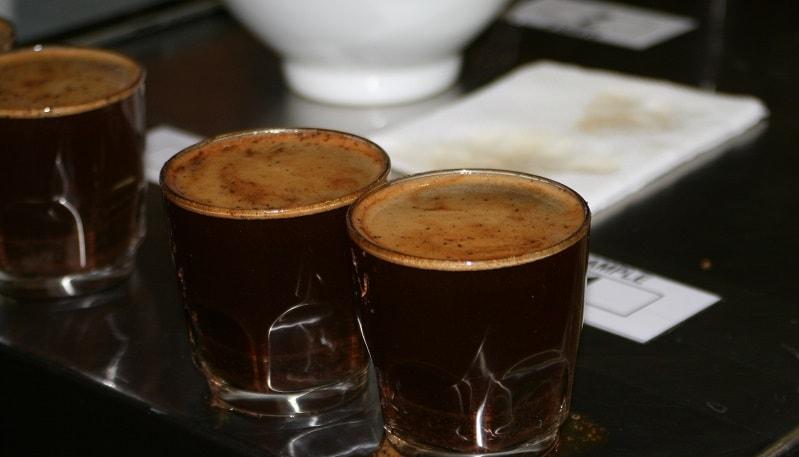 Mit Kaffee gefüllte Gläser und Notizblock dahinter
