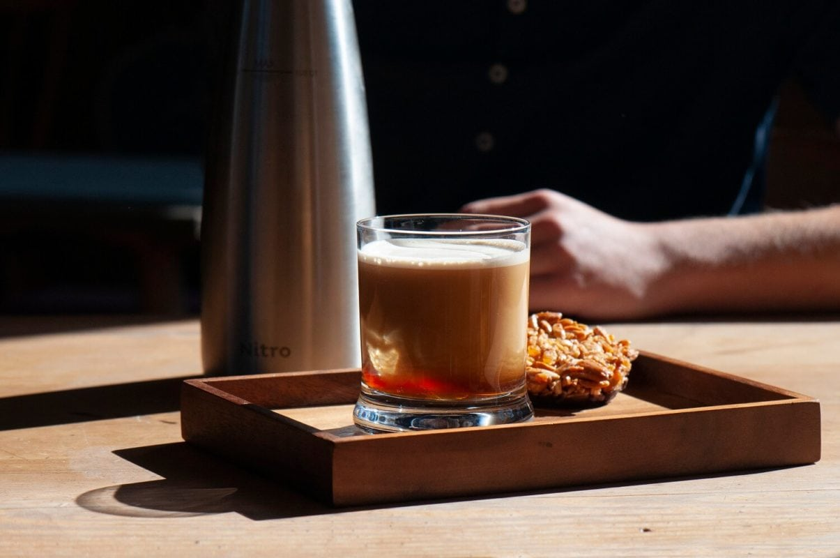 Gals mit schaumigem Nitro Coffee und Nusskeks auf Holztablet, dahinter ein Teil von einem Sahnespender und ein Teil von einem Arm