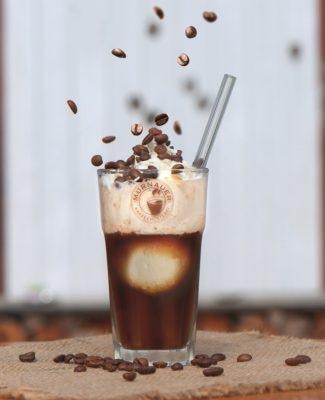 Glas mit Eiskaffee und Strohhalm, auf das von oben herunter Kaffeebohnen herabrieseln