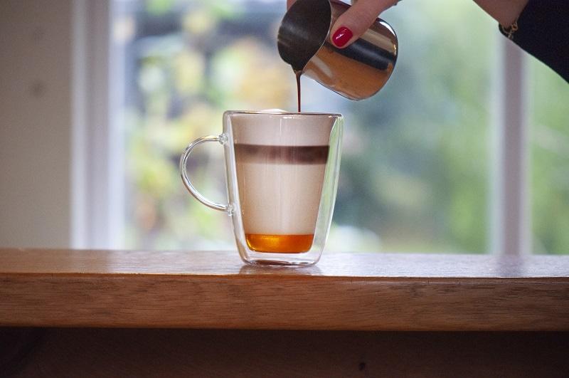 in ein Glas mit Honig am Boden und Milchschaum wird von oben ein Espresso eingegossen