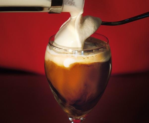 Glas voll mit Kaffee, Sahne fließt über Esslöffel rein