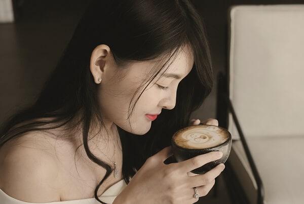 asiatische Frau beugt sich über Kaffeetasse