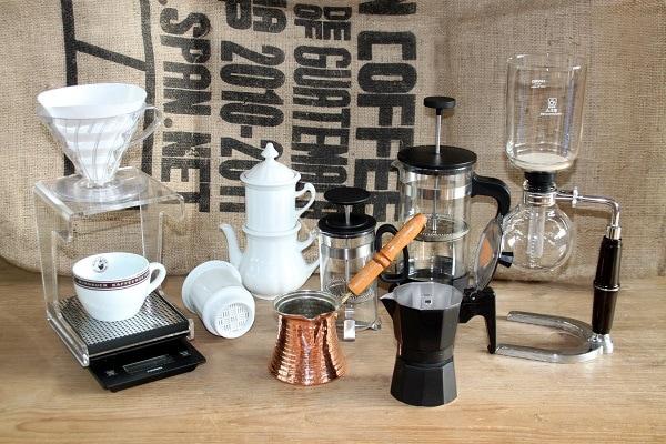 verschiedene Kaffeeutensilien zur Zubereitung stehen vor einem Hintergund mit Kaffeesack