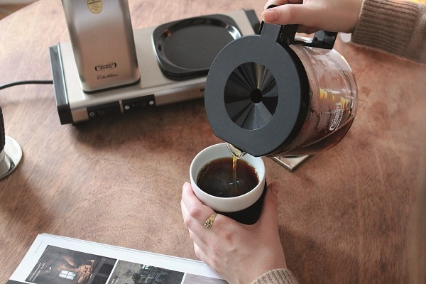 Frauenhand giesst Kaffee aus Glaskanne in eine Tasse
