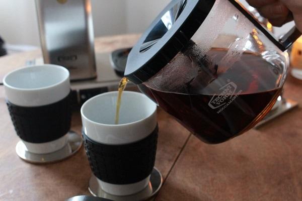 Glaskanne mit Trichter giesst Kaffee in Becher
