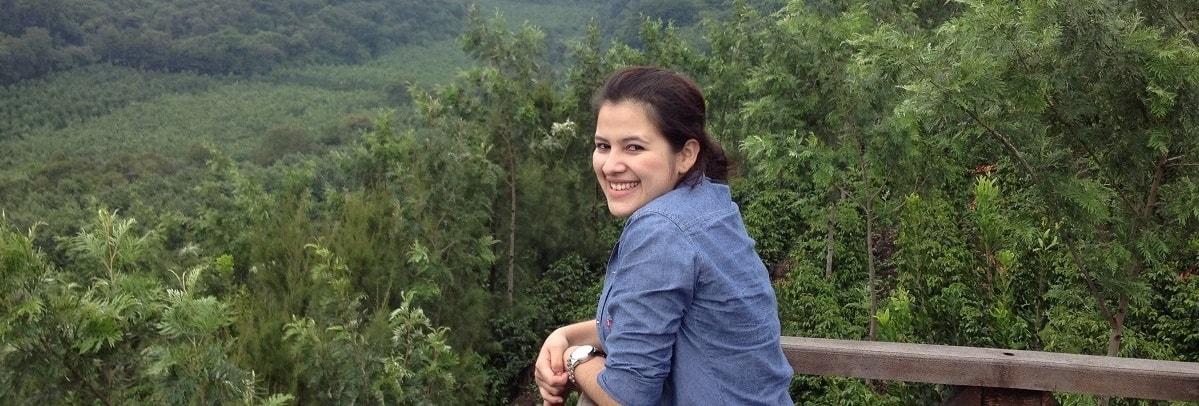 lachende Frau auf Balkon vor bewoelktem Regenwald vn Plantage San Sebastian