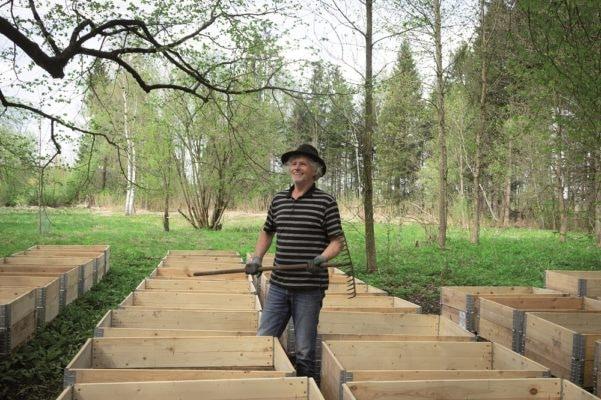 Mann mit Rechen zwischen Holzkisten auf einer Wiese
