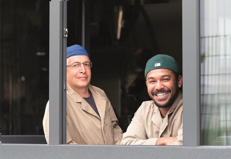 zwei Männer in Arbeitskleidung stehen an einem offenen Fenster