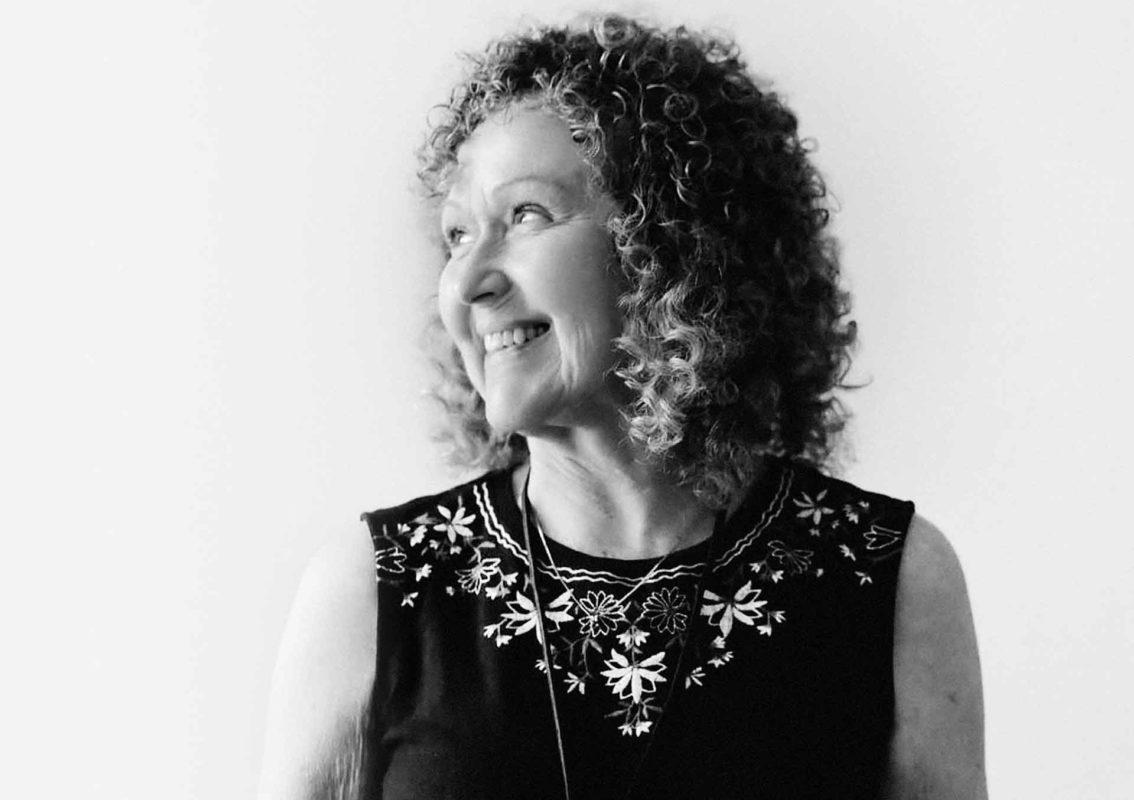 Frau mit lockigem Haar blickt auf schwazr-weiß Foto lachend nach links